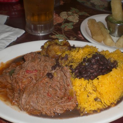 Typical Cuban dinner consisting of ropa vieja (shredded flank steak in a tomato sauce base), black beans, white rice, plantains and fried yucca.
