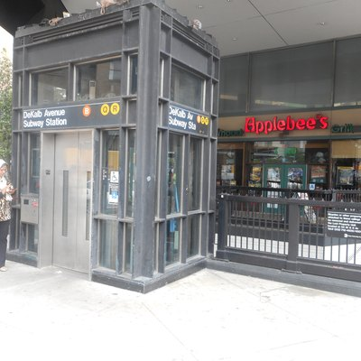 The combined staircases and elevator for the DeKalb Avenue Subway Station on the BMT Fourth Avenue Line in Downtown Brooklyn, on the southeast corner of Flatbush Avenue and DeKalb Avenue in front of an Applebee's Restaurant.