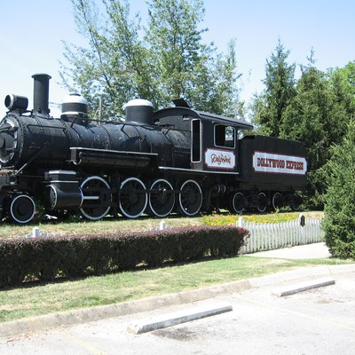 This is a photo of a 2-8-0 steam engine built by Baldwin Locomotive Works as construction number 8869. It became Smoky Mountain Railroad engine #107 and was later owned by Rebel Railroad. It is now owned by the Dollywood themepark and is on display at Hwy 441 in Pigeon Forge, TN.