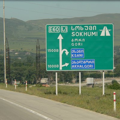 Georgian road sign on motorway S1/E60 from Tbilisi heading towards Gori. Showing Road numbers (S1/E60), as well as place names in both Georgian and Latin alphabet.