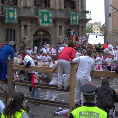 Pamplona, 7 July 2005. People climb to the fences as the bulls run by and cross the Town Hall Plaza.