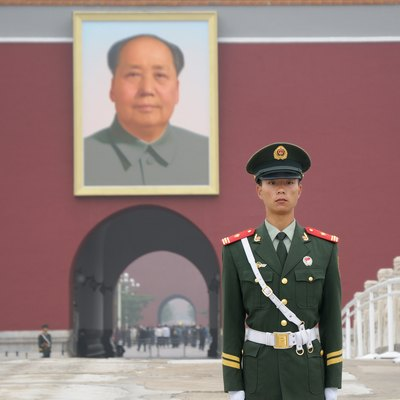 Chinese policeman guarding the southern entrance of the Forbidden City in Beijing, the Tiananmen, dominated by a giant portrait of Mao Zedong.