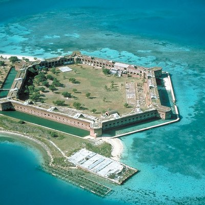 Fort Jefferson at the Dry Tortugas. The clear waters in shallow areas surrounding the fort, seen easily in the photo, are popular for snorkeling and scuba diving. Visible on the right side of the image is a breach of the sea wall caused by the direct strike of Hurricane Charley in August 2004.