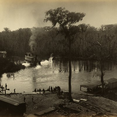 Photograph showing a group of people gathered at the shore of Silver Spring in Marion County, Florida (now Silver Springs, Florida). A steamboat heads into Silver Spring Run.