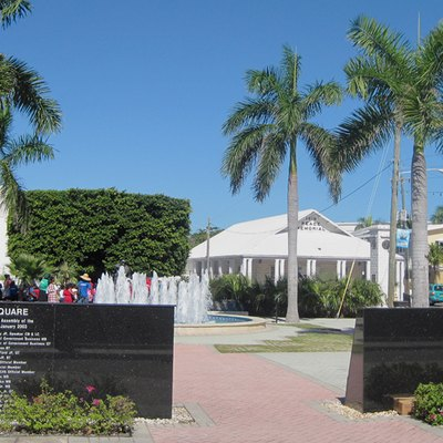 Heroes Square, commemorating Cayman Islands' war dead, is in the center of George Town. The Legislative Assembly building is at the left. The 1919 Peace Memorial is at right center, with the Town Clock to its right.