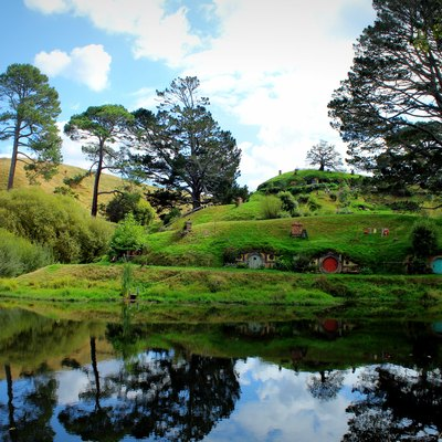 Hobbit holes reflected in water in Hobbiton, Matamata, New Zealand