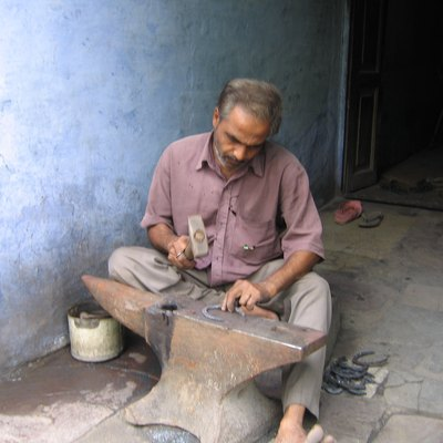 A horseshoe maker/blacksmith in India.