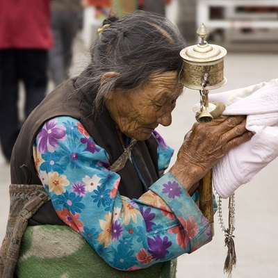 Tibet: An elderly Tibetan women holding a prayer wheel on the Lhasa's pilgrimage circuit of Barkhor. The Barkhor, a quadrangle of streets that surrounds the Jokhang Temple, is both the spiritual heart of the holy city and the main commercial district for Tibetans.