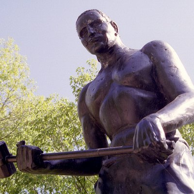 This statue of John Henry (The Steel-drivin' Man of song and legend) stands alongside State Highway 12 south of the town of Talcott, in Summers County, WV, USA. The statue is placed above the Big Bend tunnel on the C&O railroad where many believe the Man vs. Machine competition originally took place.