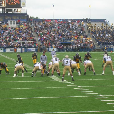 This photograph is from the portfolio of Jason DuVall. It was taken on September 30, 2006, at Dix Stadium on the campus of Kent State University in Kent, Ohio at a football game between the Kent State Golden Flashes and the Akron Zips. In the background is the south end zone of Dix Stadium, which was demolished in February 2008. The south end zone seats were originally built in 1954 as the north sideline grandstand at Memorial Stadium before being moved to Dix Stadium in 1969.
