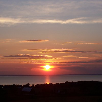 Sunset looking west over Lake Winnebago at Oshkosh, Wisconsin, taken near the top of the Niagara Escarpment by myself on June 26, 2006. Lake Winnebago is approximately 12 miles wide at this point, and the location is approximately 1 mile east the lake. The location is a State of Wisconsin run wayside where U.S. Route 151 turns due east as it climbs the Escarpment. The :Image:Brothertown Sign.jpg was taken facing the opposite direction at the same spot.
