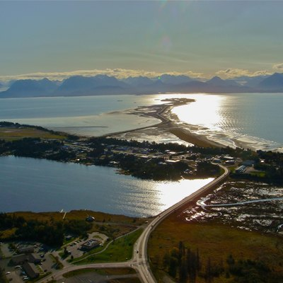 Showing a corner of Homer, Alaska Highway 1, Beluga Lake, Homer Spit, part of Kachemak Bay, and the Kenai Mountains across the bay. Homer spit is outlined by sunglint.