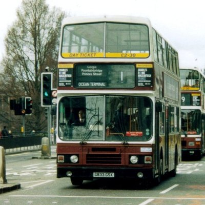 Two buses of Lothian Buses heading east on Princes Street in Edinburgh. Both wear the traditional Madder and White livery (symbolising the colour of blood from the