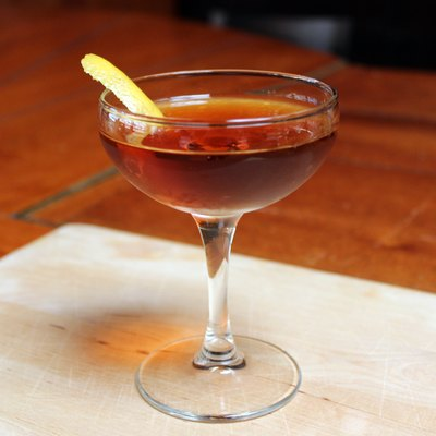 A Martinez cocktail made with gin, sweet vermouth, maraschino liqueur, Angostura bitters, and a lemon twist.