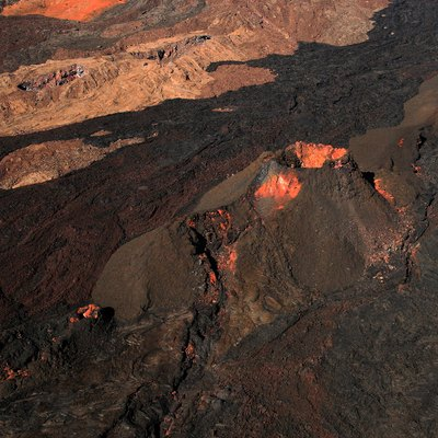 A volcanic vent and lava flows from various eruptions on the flank of Mauna Loa, photographed from a helicopter.