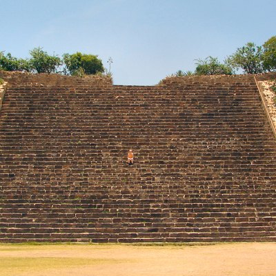 The stairs up to the South Platform in the Zapotec ruins of Monte Alban near Oaxaca, Mexico. The person sitting in the middle of the stairs to demonstrate the dimensions of the stairs is a friend of the photographer.