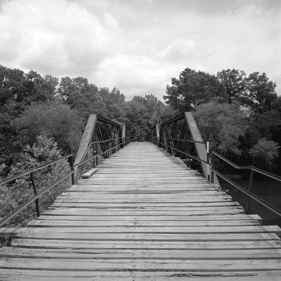 Looking west on the Mountain Fork Bridge, which carries County Road 38 over Mountain Fork Creek near Mena in Saline County, Arkansas, United States. Built in 1926, this Pratt pony truss bridge is listed on the National Register of Historic Places.