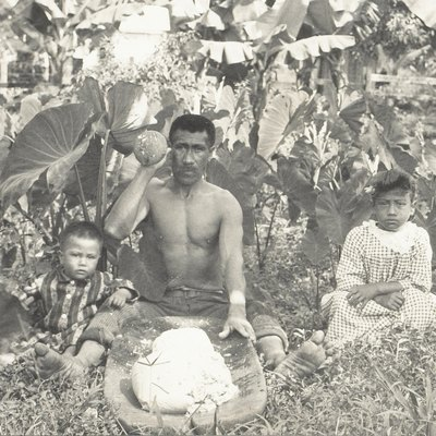 Native Hawaiian man pounding taro into poi with two children by his sides.