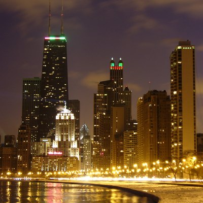 This is a photograph of Oak Street Beach in Chicago, IL on a cold night in January. The road in this picture is Lake Shore Drive. The bright, art deco building with the lit beacon is the Palmolive Building. The short building in front of the Palmolive Building is the Drake Hotel. The tall, black building behind the Palmolive Building is the John Hancock Center. The rectangular building behind and to the left of the John Hancock Center is the Water Tower Place. The tall building just right of center, with its roof lit up in red and green, is the 900 North Michigan building.