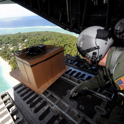 Operation Christmas Drop 2008: Tech. Sgt. Heath Bahyi and Chief Master Sgt. Michael Sundberg push out a boxed pallet of donated goods from a C-130 Hercules during Operation Christmas Drop Dec. 19 over the remote Island of Yap. Airmen today continue the tradition of delivering supplies to remote islands of the Commonwealth of the Northern Marianas Islands, Yap, Palau, Chuuk and Pohnpei. In all, more than 180 boxes were built for the humanitarian mission, making 2008 one of the largest drops in Operation Christmas Drop's 57-year history. Sergeant Bahyi and Chief Sundberg are loadmasters from the 36th Airlift Squadron from Yokota Air Base, Japan.