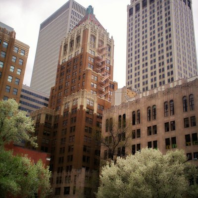 Several buildings in downtown Tulsa, Oklahoma. Philtower: Orange, brick building in the center foreground; Mid-Continent Tower: to the right of Philtower with the greenish roof; First Place Tower: to the left of Philtower.