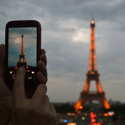 A man taking a photograph of the illuminated Eiffel Tower on his smartphone at dusk.