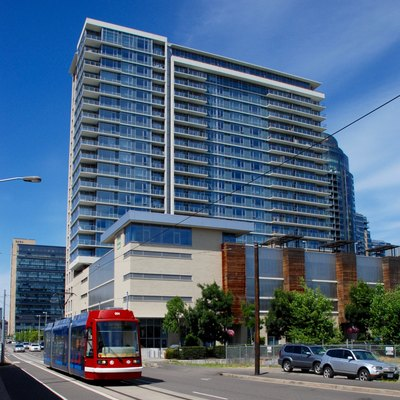 Riva on the Park, a 22-story apartment building in Portland, Oregon's South Waterfront district, viewed from the south-southwest. In the foreground, a streetcar is southbound on Moody Avenue. In the background is the OHSU Center for Health and Healing, built in 2006.