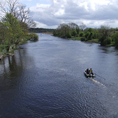 Looking downriver from the bridge over the Shannon at Drumsna, County Leitrim. Fishermen in a dinghy.