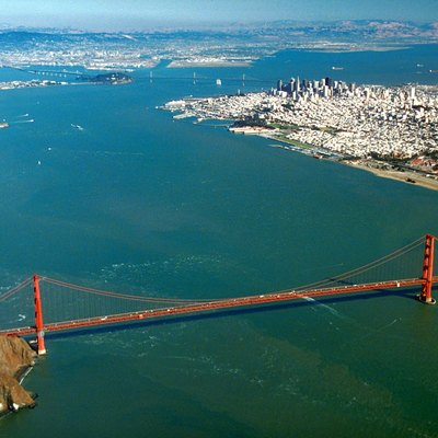 Aerial view of the Golden Gate and the central portion of San Francisco Bay. The Golden Gate bridge is in the foreground and the Bay Bridge is in the distance. The city of San Francisco is to the right with Alcatraz Island in the middle of the bay at left center. Oakland lies across the bay in the far distance.