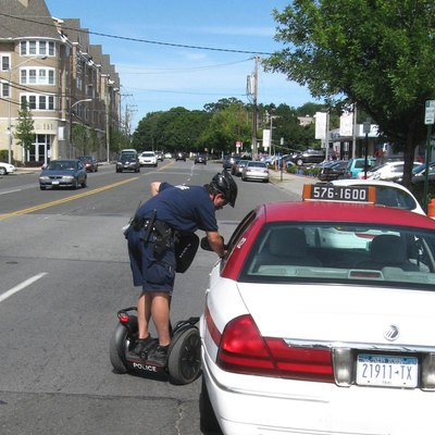 Looking northeast on Boston Post Road as a w:New Rochelle, New York policeman talks to a taxi driver without dismounting from his w:Segway on a sunny midday.