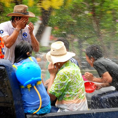 People on the back of a truck get soaked during the Songkran festival in Chiang Mai, Thailand