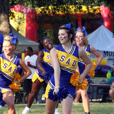 Southern Arkansas Mulegating: the cheerleaders rally school spirit while people enjoy the food and games provided in the background during SAU's Family Day.