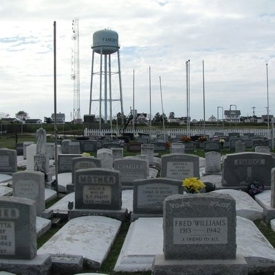 One of Tangier's newer cemeteries. The flagpoles mark the graves of veterans. The playground is just beyond the picket fence and the school is on the far right. The island's airstrip is beyond the water tower, across West Ridge Road.