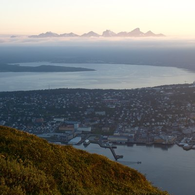 City of Tromssa in midnight in Midnight sun, photographed from above from the mountain nearby, some mountains in the horizon.