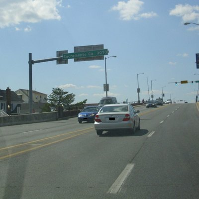 Westbound view on US Route 50, Ocean Gateway, leaving Ocean City, MD. Sign displays distance to Sacramento, CA, 3073 Miles.