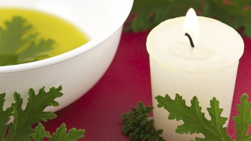 <p>Citronella oil with candle and leaves.</p>