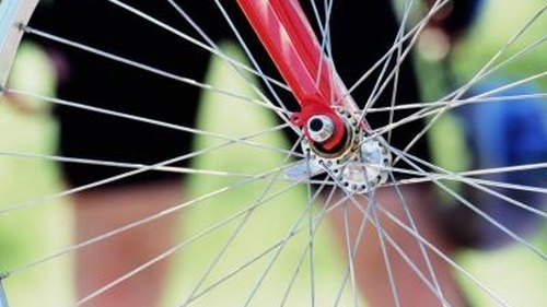 <p>Wire spokes and an axle, two different applications of steel in a bicycle wheel.</p>
