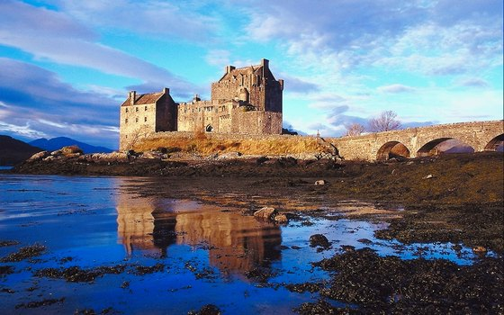 Visitors cross a small bridge to visit Scotland's mysterious Eileen Donan Castle.