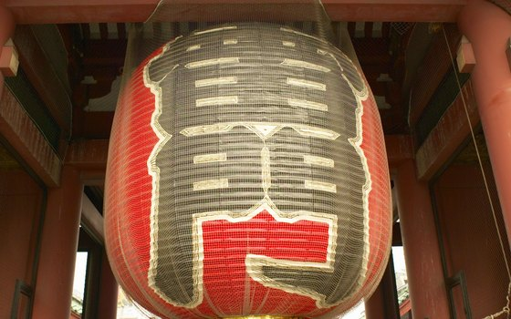 Enter a walkway to Sensoji Temple under the tall red gates and gigantic lantern.