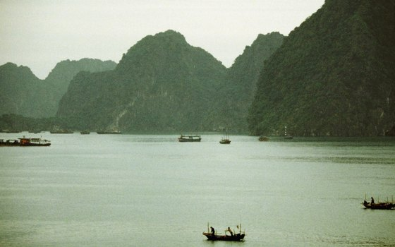 Take a boat tour of Halong Bay to see the vegetation-covered karst formations.