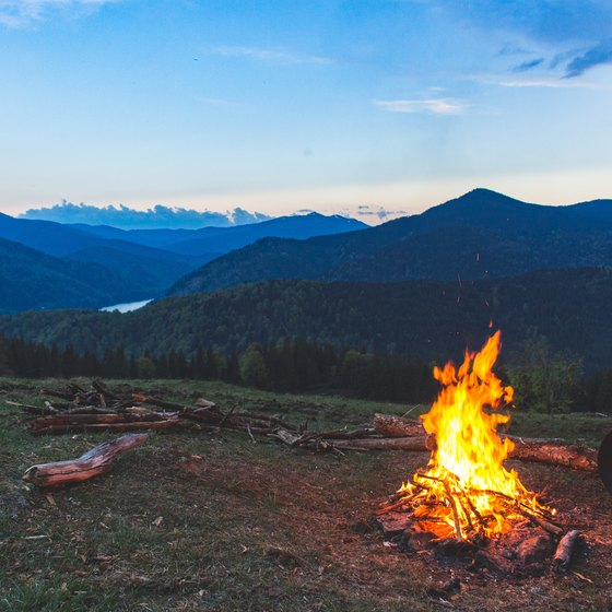 A bonfire in the woods and nice scene of the hills and mountains.