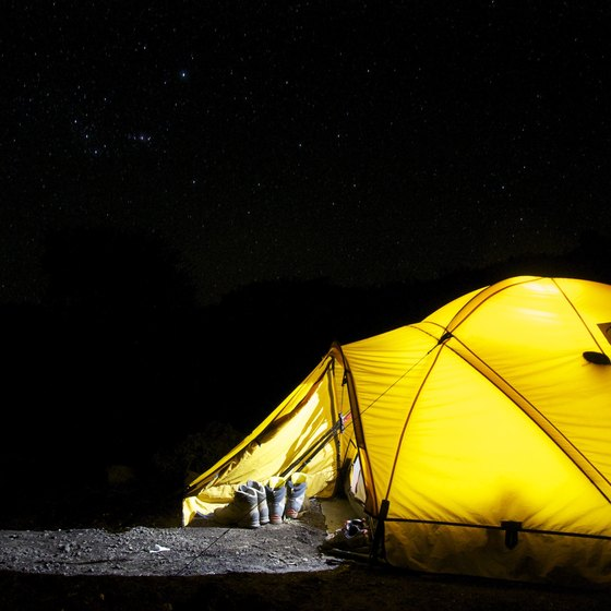 A yellow tent camping in the pitch dark night.