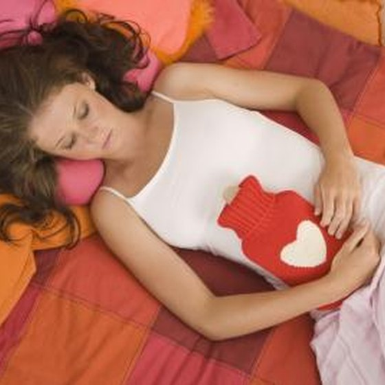 Young girl laying on bed with hot water bottle against stomach.