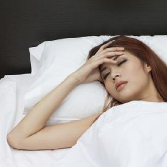 Young woman holding her head while in bed.