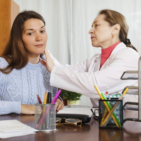 A woman having her ear exam end by a doctor.