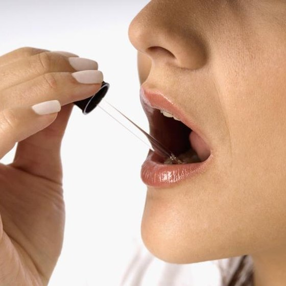 Woman with medicine dropper in her mouth