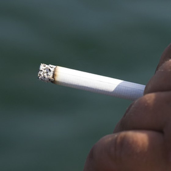 Smoking cigarettes causes tar stains that discolor teeth.