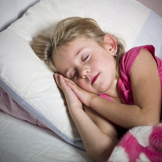 A young girl sleeping in her bed