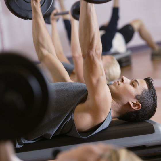 The barbell bench press is an ideal exercise for flattening the chest.