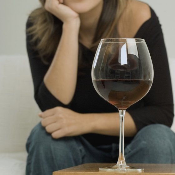 A glass of red wine in front of a woman sitting on a sofa.
